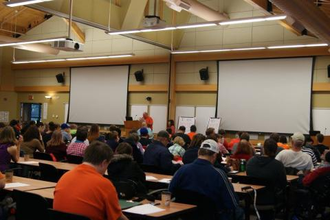 A large classroom with two drop-down screens, a presenter in a blue shirt and conference participants sitting at tables.
